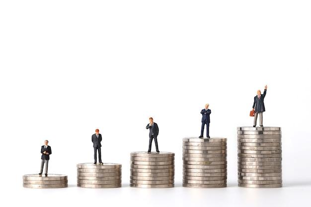 Miniatuur mensen zakenman staande stapelen munten podium