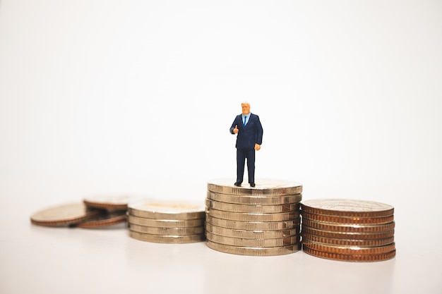 Miniatuur mensen, zakenman tonen goed werk symbool op stapel munten