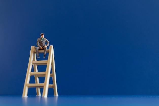 Miniatuur mensen zakenman zittend op de trap en ruimte voor tekst. bedrijfsgroeiconcept