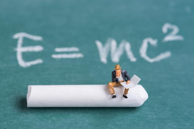 Miniatuur mensen zitten op krijt stok met de relativiteitstheorie theorie achtergrond