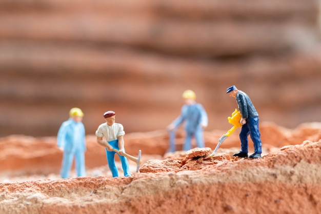 Miniatuur mensenarbeider team dat bakstenen bevestigt tijdens de bouw van een huis, bouwconcept