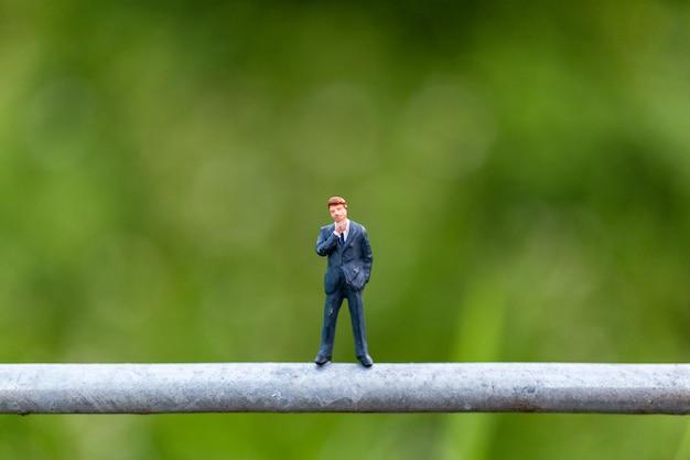 Miniatuur mensenconcept met zakenmantribune op een draad