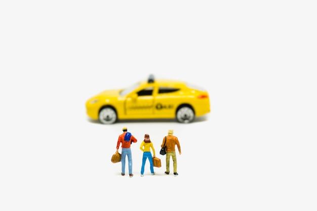 Miniatuur mensenman en vrouwen wachtende die taxi op witte achtergrond wordt geïsoleerd