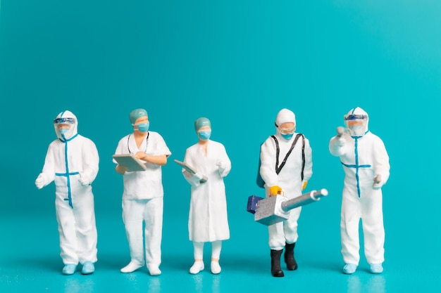 Miniatuur mensenteam van artsen, mannen en vrouwen die ziekten en virussen bestrijden, gezondheidszorgconcept Premium Foto