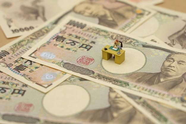 Miniatuur mensenzakenlieden die met japanse bankbiljetten met een waarde van 10.000 yen zitten