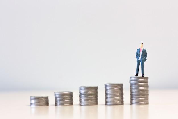 Miniatuur mensenzakenlieden die zich bovenop stapel muntstukken bevinden.