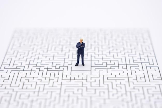 Miniatuur mensenzakenlieden die zich in het centrum van het labyrint bevinden. business idee