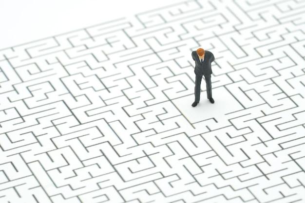 Miniatuur mensenzakenlieden die zich in het centrum van het labyrint bevinden.