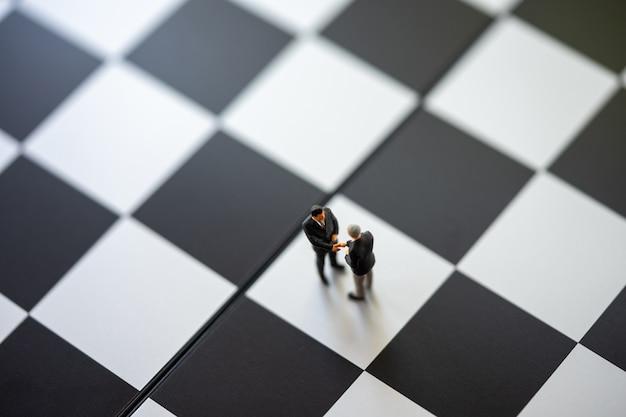Miniatuur mensenzakenlieden die zich op een schaakbord met een schaakstuk bevinden
