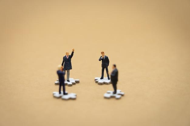 Miniatuur mensenzakenlieden die zich op witte figuurzaag bevinden
