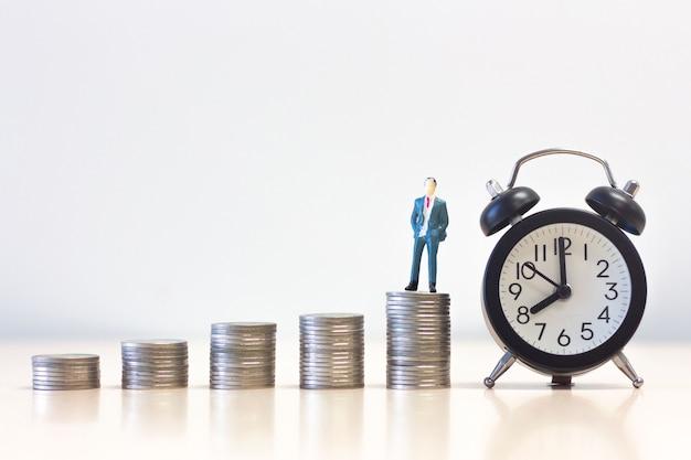 Miniatuur mensenzakenman die zich op de stapel van het geldmuntstuk met wekker bevinden