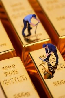 Miniatuur mijnwerker graaft op goudstaaf