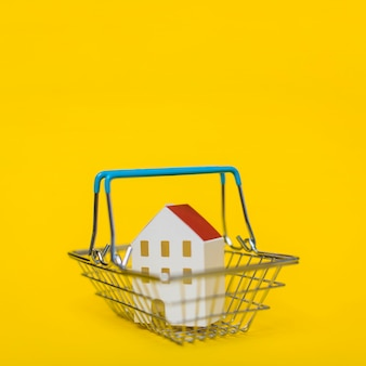 Miniatuur model van huis in het winkelwagentje tegen gele achtergrond