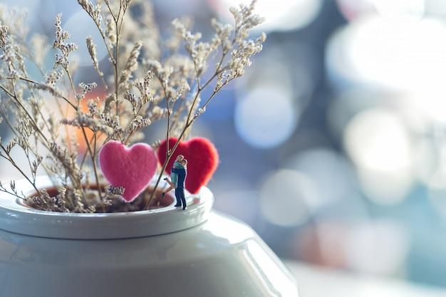 Miniatuur paar die voor mooie bloemachtergrond koesteren