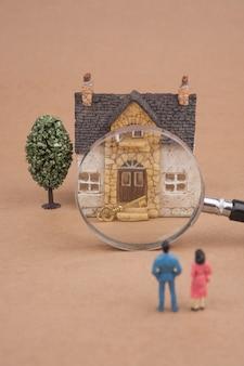 Miniatuur paar kijken naar nieuw huis