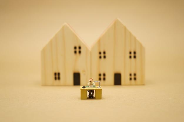 Miniatuur persoon die vanuit huis werkt