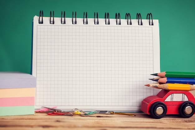 Miniatuur rode auto met een kleurrijke potloden en rode appel op houten tafel. terug naar school-concept