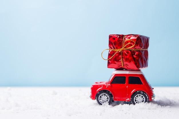 Miniatuur rood autostuk speelgoed die giftdoos leveren op blauw