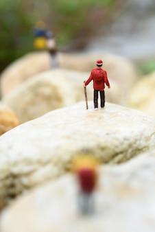 Miniatuur rugzakreizigers die rots, reisconcept wandelen