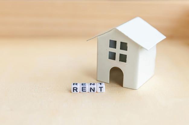 Miniatuur speelgoed model huis met inscriptie huurbrieven woord op houten achtergrond