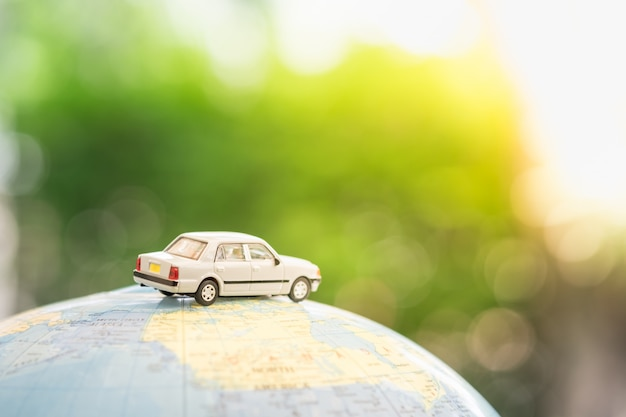 Miniatuur speelgoedauto op wereldkaart ballon met groene natuur