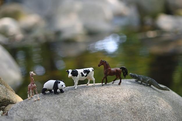 Miniatuur speelgoeddieren op rotsen in de rivier.