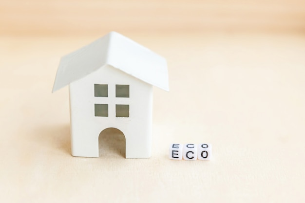 Miniatuur speelgoedmodel huis met inscriptie eco letters woord. eco village, abstracte milieuachtergrond. ecologie nul afval sociale verantwoordelijkheid recycle bio huisconcept