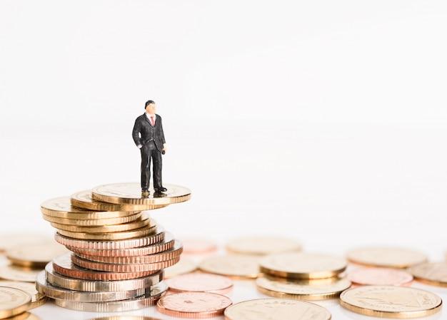 Miniatuur succesvolle zakenmensen staan bovenop gouden geldmunten geïsoleerd op een witte achtergrond, hoog risico hoog rendement concept