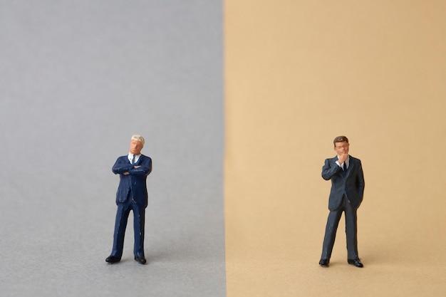 Miniatuur twee zakenlieden staan aan weerszijden