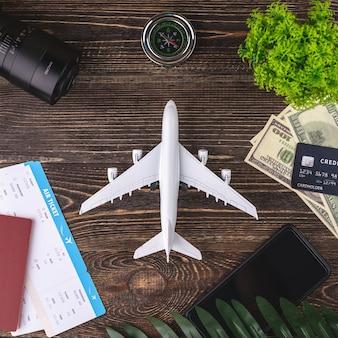 Miniatuur van een vliegtuig op een houten tafel met kaartjes, documenten, geld en andere reisaccessoires