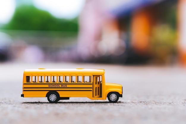 Miniatuur van gele schoolbus op de weg