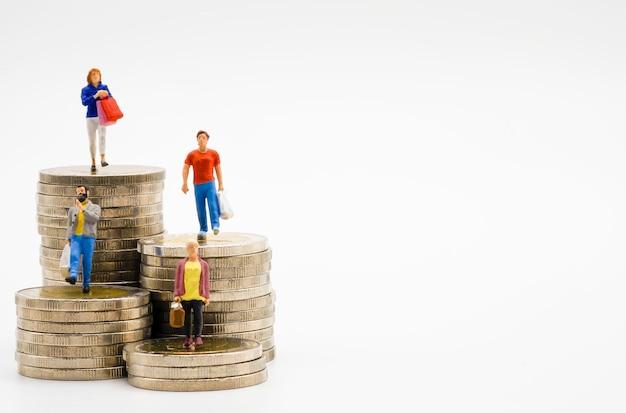 Miniatuur van winkelende vrouwen en mannen op muntstukken die met witte achtergrond stapelen.