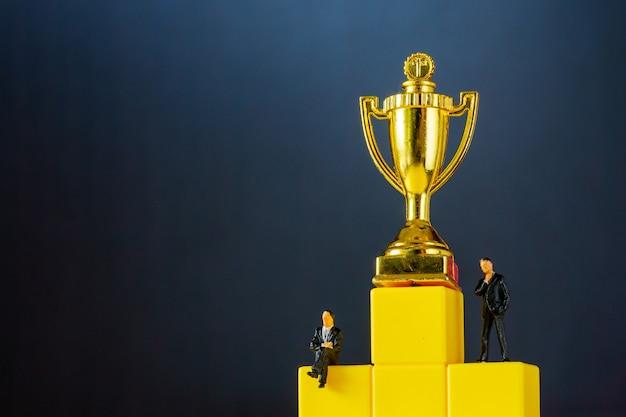 Miniatuur van zakenman staat op podiumladder met gouden trofee op zwarte ondergrond