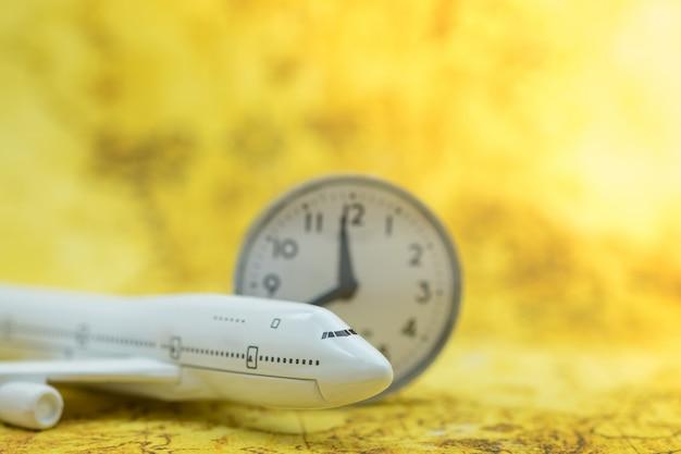 Miniatuur vliegtuig speelgoed model met vintage ronde klok op wereldkaart.