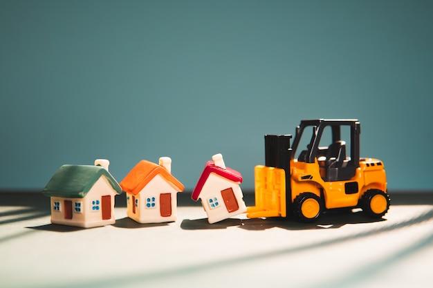 Miniatuur vorkheftruck die minihuis opheft dat als concept van bezitonroerende goederen gebruikt
