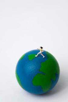Miniatuur vrouw draait op wereldbol op wit