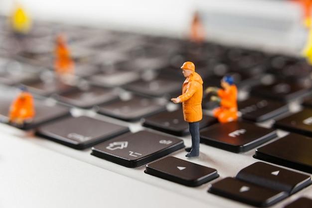 Miniatuur werklieden repareren van een laptop toetsenbord