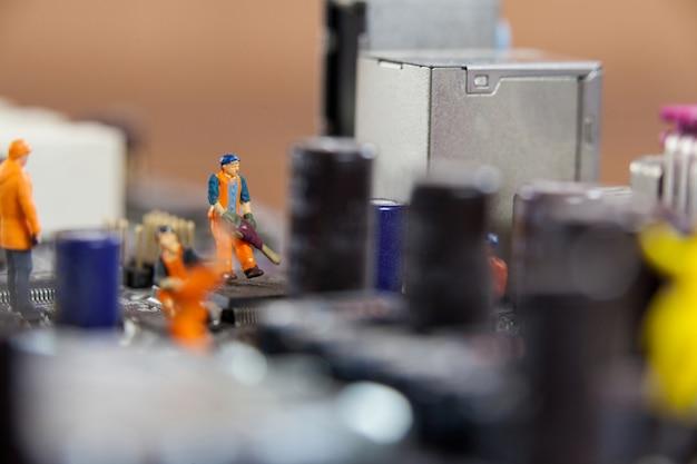 Miniatuur werknemers die op de chip van het moederbord