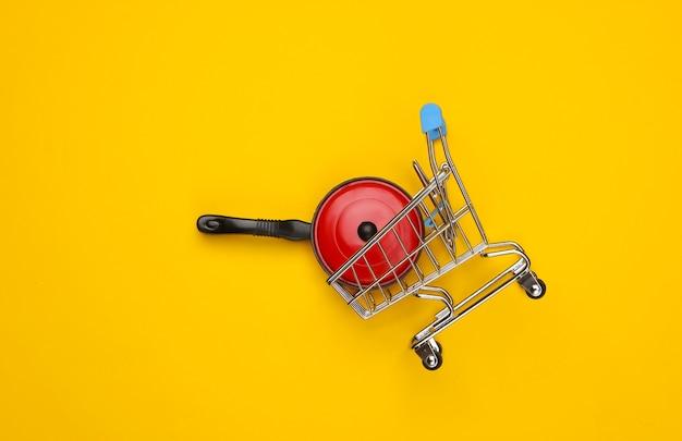 Miniatuur winkelwagentje met pan op geel.