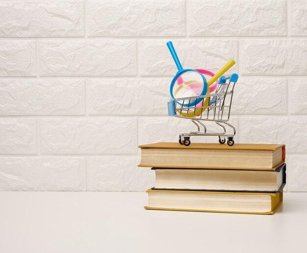 Miniatuur winkelwagentje staat op een stapel boeken, witte bakstenen achtergrond, bestel boeken online, kopieer ruimte