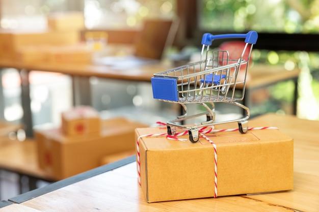 Miniatuur winkelwagentjes op pakketdoos. online winkelen en e-commerce.