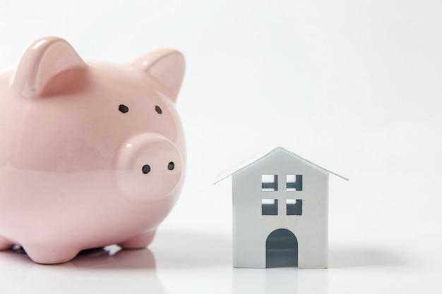 Miniatuur wit stuk speelgoed huis en spaarvarken op witte achtergrond