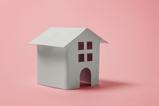 Miniatuur wit stuk speelgoed huis op roze achtergrond