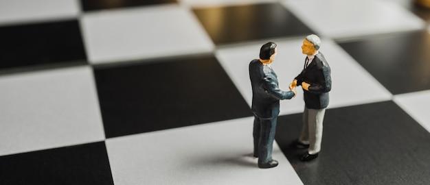 Miniatuur zakelijke partnerschap handdruk concept. succesvol zakenliedenhandenschudden na goede deal.