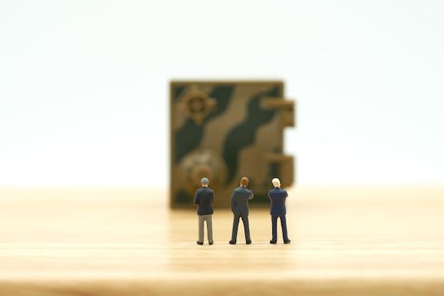 Miniatuur zakenlieden die de sleutel van de beveiligingsanalysebeveiliging bevinden