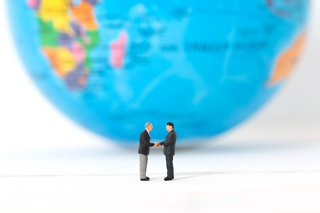 Miniatuur zakenlieden die handen op vage globale of wereldachtergrond schudden.