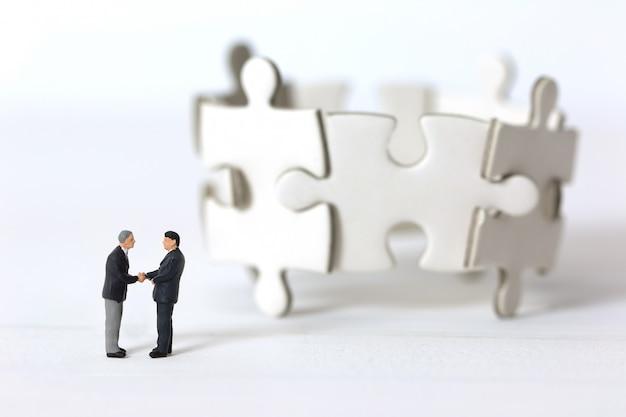 Miniatuur zakenlieden die handen op vage groep puzzelachtergrond schudden.