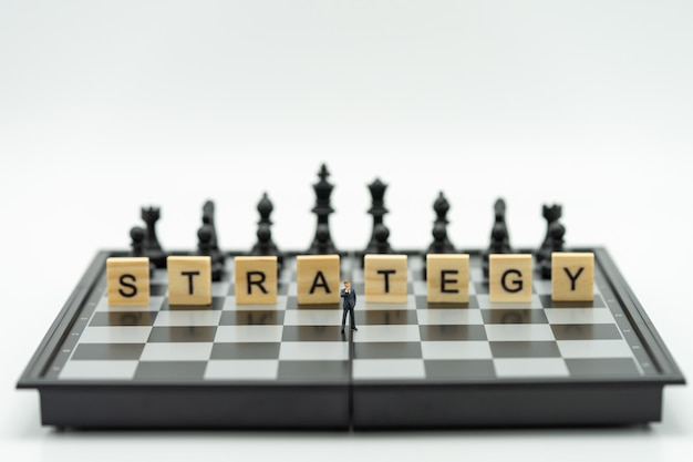Miniatuur zakenlieden die zich op een schaakbord met een schaakstuk bevinden