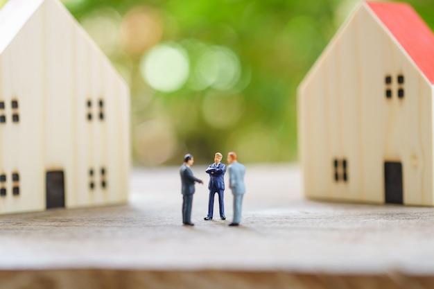 Miniatuur zakenlieden staande investeringsanalyse huisvesting of investering in roerende goederen.