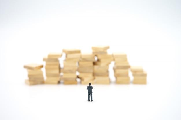 Miniatuur zakenman die zich met stapel bankbiljetten bevindt